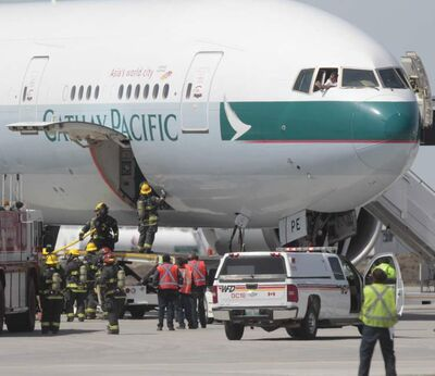 Firefighters open the cargo door of a plane diverted to Winnipeg to check for fire inside.