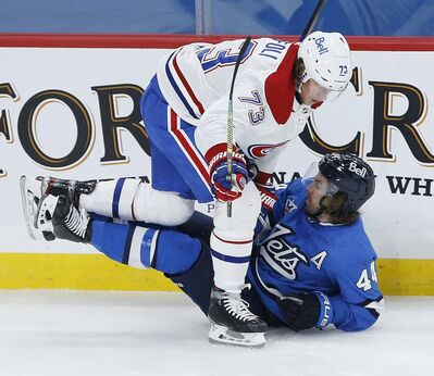 Winnipeg Jets' Josh Morrissey and Montreal Canadiens' Tyler Toffoli collide during the second period. THE CANADIAN PRESS/John Woods