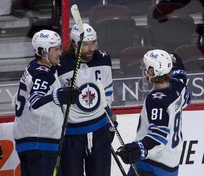 Winnipeg Jets' Mark Scheifele, left, and Kyle Connor, right, congratulate Blake Wheeler on his goal during the second period of their 4-1 win over the Ottawa Senators on Thursday in Ottawa. THE CANADIAN PRESS/Adrian Wyld