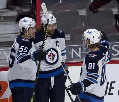 """Winnipeg Jets' Mark Scheifele, left, and Kyle Connor, right, congratulate Blake Wheeler on his goal during second period NHL action against the Ottawa Senators on Thursday. THE CANADIAN PRESS/Adrian Wyld</p> <p>""""> </a><figcaption readability="""