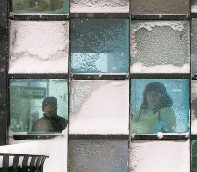 Robert F. Bukaty / The Associated PressRiders wait in a bus stop where snow collects during a storm Friday in Portland, Maine.