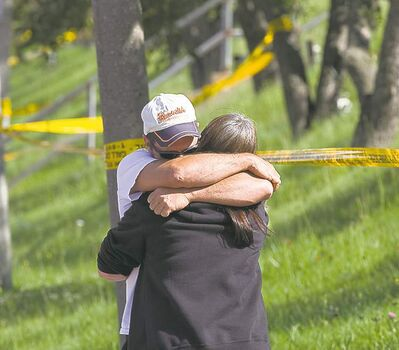 Chris Young / The Canadian PressElliot Lake residents comfort each other after learning the rescue was called off.