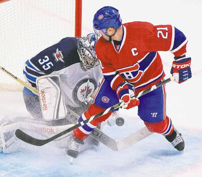 The Montreal Canadiens' Brian Gionta struggles with the puck in front of Jets goalie Al Montoya during third-period NHL action in Montreal on Sunday.