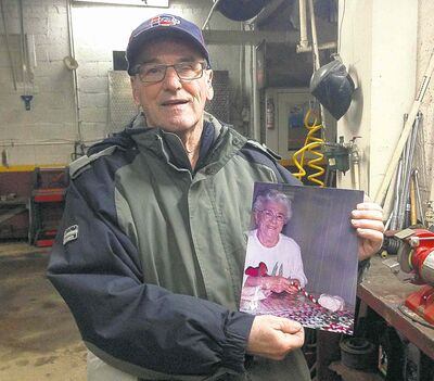Marc-Henri Saindon holds a photo of his mother, Marie-Jeanne Gagnon, 99, who was killed in the fire.