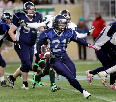 West Kildonan Wolverines running back Tyler Byron (#21) sprints through traffic Thursday at Investors Group Field against the Elmwood Giants.