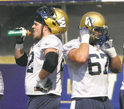 Winnipeg offensive linemen Steve Morley (left) and Chris Kowalczuk take a brief breather during practice Tuesday at Canad Inns Stadium.