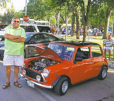 Ken Benoit, with his 1978 Mini on Memorial Blvd. last Friday. 'Maybe now, when the police see a collector plate, they'll realize it's just a bunch of old farts out having a good time...""