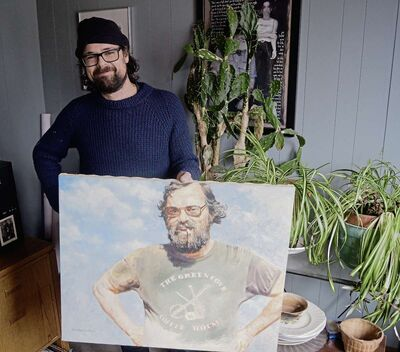 Leonard Podolak is pictured in the office of Home Routes/Chemin Chez Nous holding a portrait of his father, Mitch Podolak. The second annual Winnipeg Crankie Festival honoured the late co-founder of the Winnipeg Folk Festival.