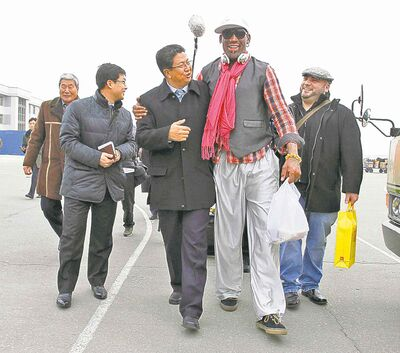 Dennis Rodman walks arm-in-arm with North Korea's Sports Ministry vice-minister Son Kwang Ho on arrival at Pyongyang International Airport Monday.