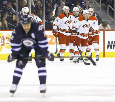 Winnipeg Jet Olli Jokinen glides glumly out of the area as the Carolina Hurricanes celebrate a goal by captain Eric Staal (12).