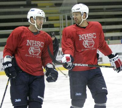Andrew Ladd and Eric Fehr talk as they skate at the Iceplex this morning.