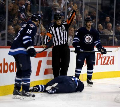 The referee summons trainers and medical personnel after Jacob Trouba crashed head-first into the boards during the second period of Friday night's game.