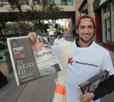 Brad Morrison hands out free Winnipeg Free Press newspapers on Portage Avenue and Carlton Street  Wednesday with the launch of the newspaper's augmented reality feature. Readers can use the Blippar app to scan newspaper pages and access interactive content.