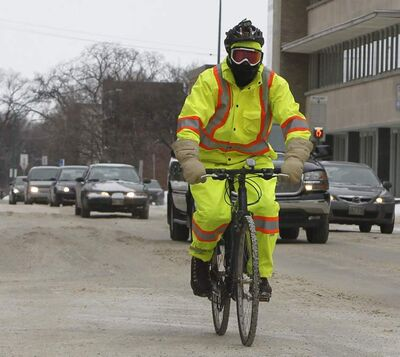 A hardy winter cyclist wearing proper high-visibility clothing shares the road with motor vehicles downtown on Friday. Collisions between bicycles and cars are starting to edge up, data show.