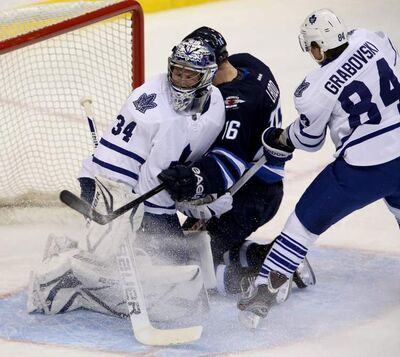 Winnipeg Jets forward Andrew Ladd runs into Toronto Maple Leafs goaltender James Reimer after being pushed into the net by Leafs defenceman Mikhail Grabovski during first-period NHL action in Winnipeg, Tuesday. The Jets beat the Leafs 5-2.