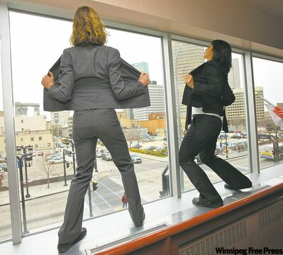 Ali Robson (left) and Natasha Torres-Garner dance above downtown pedestrians and drivers.