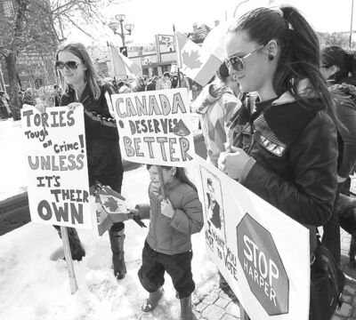 Christa Bishop (right) and others gather at River Avenue and Osborne Street from where they plan to walk to MP Joyce Bateman's office on Corydon Avenue.