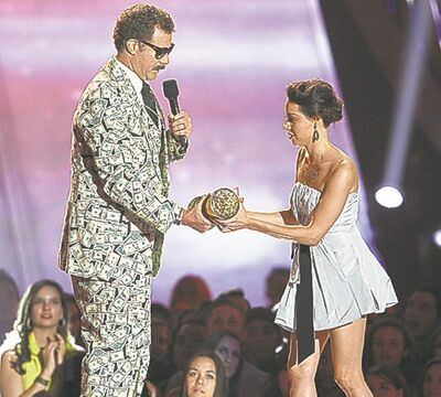 Aubrey Plaza, right, as she tries to take away an award presented to Will Ferrell during the 2013 MTV Movie Awards.