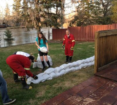 Residents of Swan River sandbag a property after a state of emergency was declared.