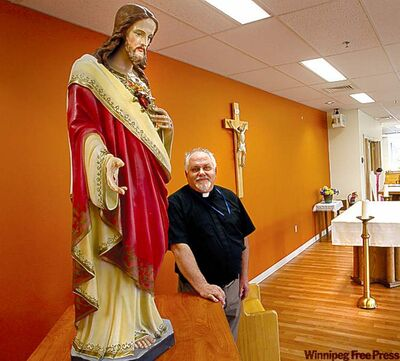 Rev. Vince Herner, spiritual care director at Misericordia Health Centre, with statues and a crucifix from St. Luke's Chapel.