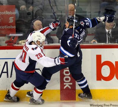 Winnipeg Jets defenceman Dustin Byfuglien (33) collides with Washington Capitals winger Troy Brouwer in second-period action Thursday at the MTS Centre.