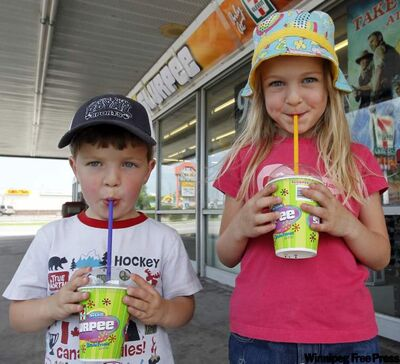 Three-year-old Mason Volkart (left) and his sister Calla, 5, enjoy a Slurpee from the 7-Eleven on Henderson Highway Monday afternoon. Manitoba has once again been crowned the Slurpee Capital of the World, the 12th consecutive year the province  has clinched the title.