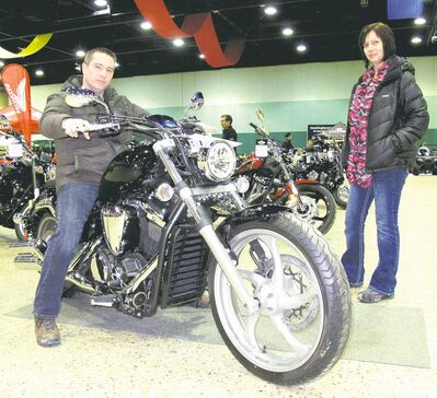 Colin Nault sizes up a Yamaha motorcycle while Tavona Molinski offers that much-needed look of approval.