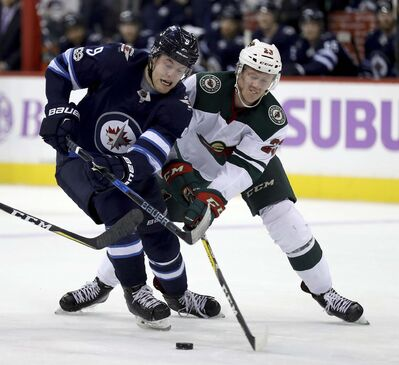 <p>Winnipeg Jets' Andrew Copp and Minnesota Wild's Gustav Olofsson battle for the puck during the second period, Monday.</p>