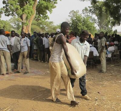 Men carry a 100-kilogram bag of millet as they leave a distribution centre in western Niger.