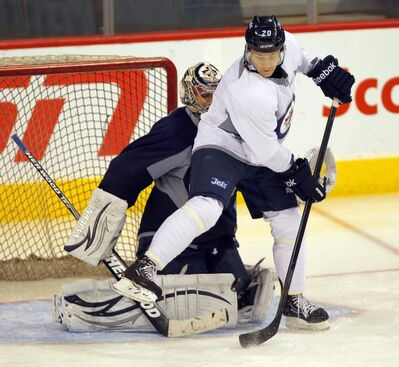 FILE - Jets goalie Ondrej Pavelec defends the net as Jets Antti Miettinen tries to deflect the puck past him during the Winnipeg Jets pre-game skate at the MTS Centre.