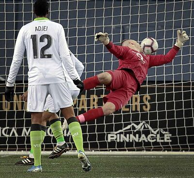 Valour FC net minder Tyson Farago dives in vain for the ball as York9 FC's Simon Adjei Karlsson watches his team score their third unanswered goal Wednesday at IG Field.