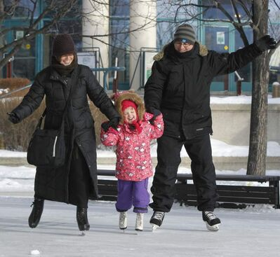 Skaters make their way around the rink under the canopy at The Forks market.