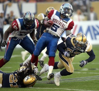 Als running back Noel Devine finds a hole between Bombers defenders Alex Suber (left) and Desia Dunn during the first regular-season game at Investors Group Field.