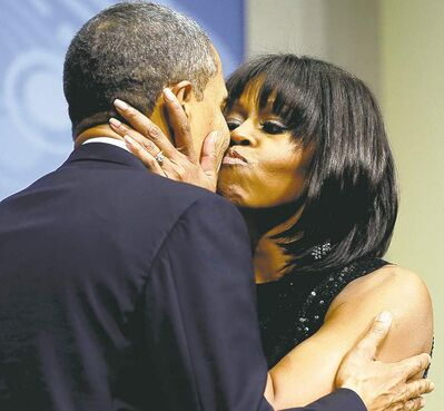 Charles Dharapak / The Associated PressBarack Obama and his wife, Michelle, sneak a kiss during an inaugural reception on Sunday.