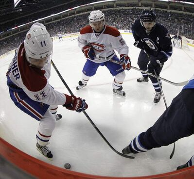 Montreal Canadiens' Brendan Gallagher (11) and David Desharnais (51) battle with Winnipeg Jets' Andrew Ladd (16) and Mark Stuart (5) in the corner during the first period of NHL action at the MTS Centre in Winnipeg, Thursday.