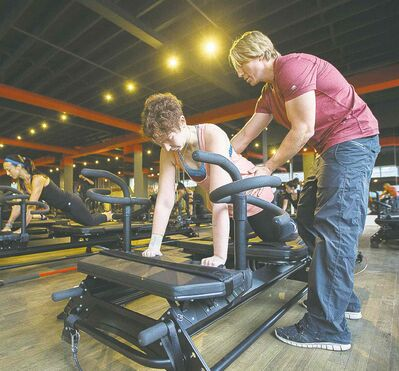 Sebastien Lagree helps reporter Rebecca Tucker through an intensive workout on the Megaformer.
