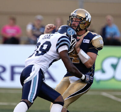 Bombers QB Buck Pierce takes one on the chin from the Brandon Isaac of the Argos on Saturday.