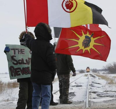 Protesters on the CN rail tracks that cross the Yellowhead Highway west of Portage la Prairie. The CN Rail police were on the scene to alert the conductor, and the westbound train stopped about a kilometre away from the protesters.