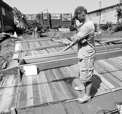 JOE BRYKSA / WINNIPEG FREE PRESS  James Deighton stands on the roof of his cottage. Only 24 hours earlier, it had been where it belonged-- on top of his cottage  in the background.
