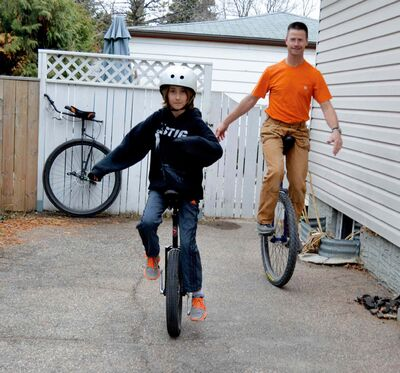 Keith Holm and his son, Aidan, show off their unicycling skills.