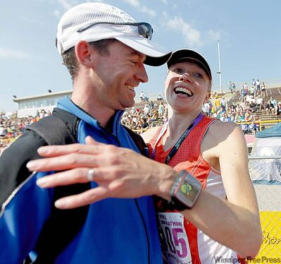Cindy Sondag of Grand Forks, N.D., celebrates her second straight women's marathon win with husband Eric Sondag.