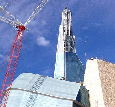 A crane lifts the last piece of glass on the Canadian Museum For Human Rights Thursday morning.