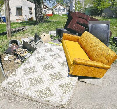 A dumped mattress, sofas and other larger garbage litter an empty lot off a back lane in the North End.