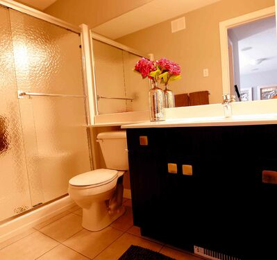 A short hallway leads to a three-piece ensuite bathroom with a tile floor and a five-foot shower.