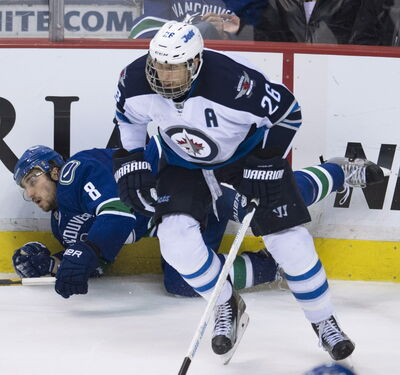 Winnipeg Jets' Blake Wheeler (26) knocks over Vancouver Canucks' Chris Tanev (8) during the third period of NHL action in Vancouver, B.C.  March. 24.