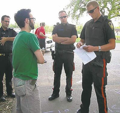 Police talk to chalk artist Graham Hnatiuk on Aug. 10.