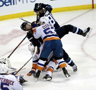Winnipeg Jets' Mark Scheiflele gets tackled by the Islanders' Casey Cizikas and Adam Pelech during a scrum in front of the Islanders' net, Thursday. There was no penalty on the play.