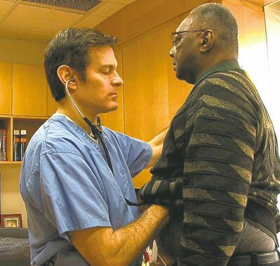 Dr. Mehmet Oz examines a patient in NY Med documentary series.
