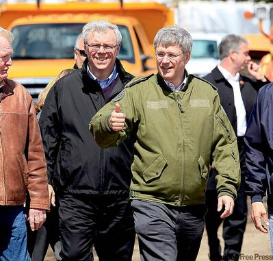 Prime Minister Stephen Harper salutes workers as he tours the flood zone with Premier Greg Selinger last week.