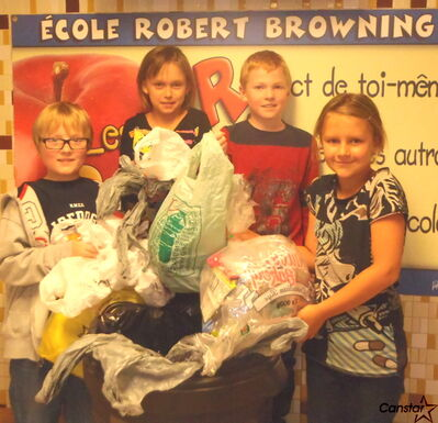 A group of Grade 4 students from Ecole Robert Browning show off some of the bags they've collected so far.